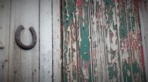 En hestesko henger ved siden av en vindskjev dør, der malingen har flasset av.