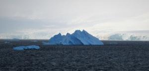 Et majestetisk isfjell i blåtoner mot den hvite naturen.