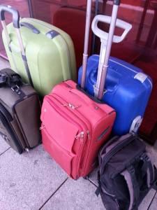 Bilde av en grønn, blå, militærgrønn og rød koffert, samt en sort ryggsekk.