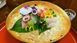 Gullfarget fat med rå fisk, dandert med blomster og pynt.