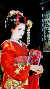 En geisha i rød kimono, hvitpudret ansikt og oppsatt hår.
