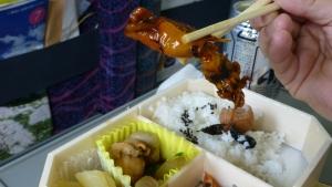 En syltet blekksprut holdes mellom to pinner. Under ser vi ris og andre ingredienser.