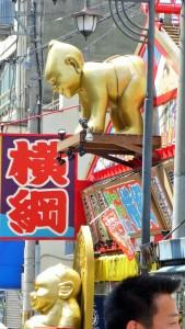 Gateskilt o Osaka med japanske tegn og en gullfarget sumobryter i plast.
