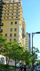 Gult hotell som har baksiden av et kapell stikkende ut fra veggen i åttende etasje.