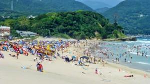 Strand med fargerike parasoller og mange mennesker.