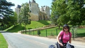 Kristin på sykkel i forgrunnen med slott i bakgrunnen.
