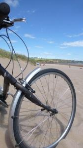 Sykkelhjul i sand med sjø i bakgrunnen.