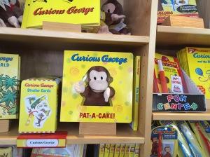 bokhylle med Nysgjerrige Nils bøker, pluss en dukke av Nils.