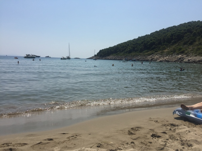 strand og sjø med båter.