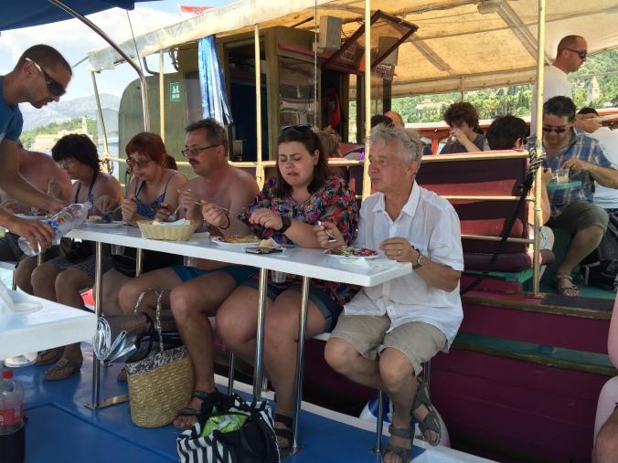 personer på en båt, sittende på en benk og spiser.