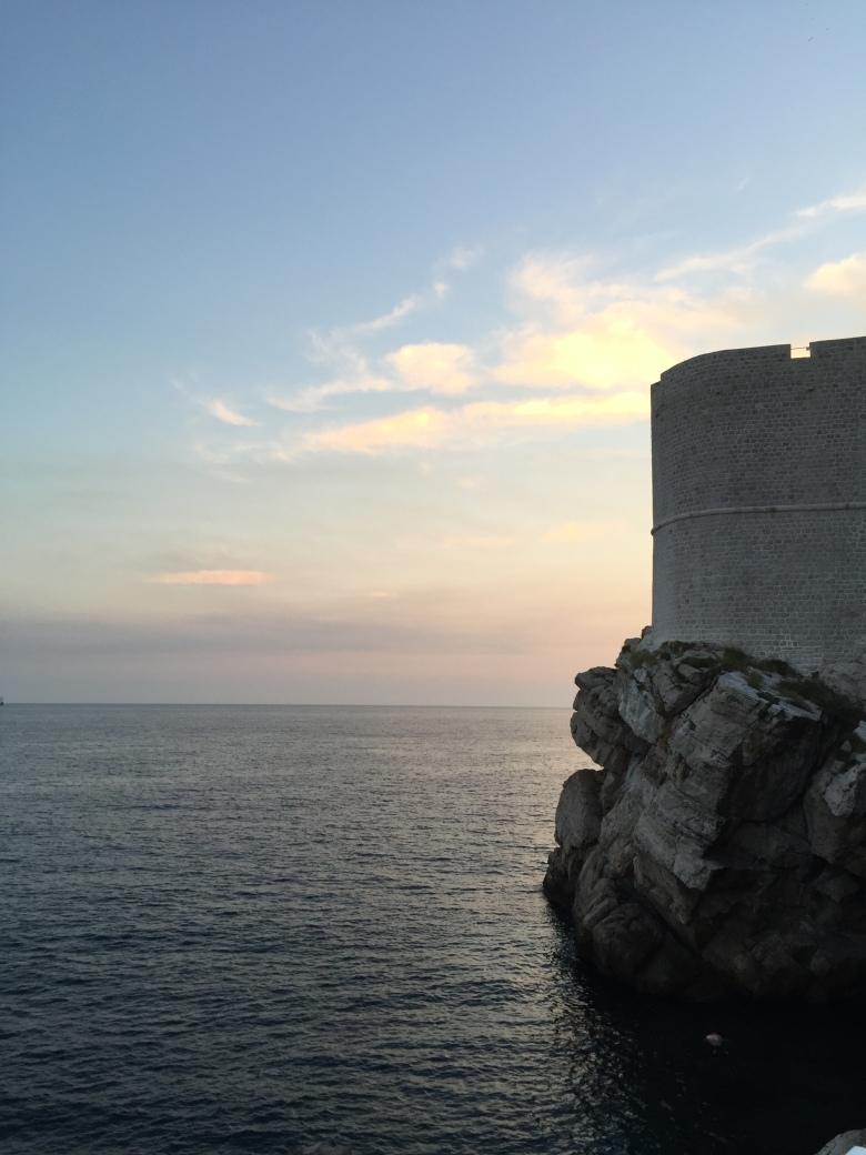 sjø, klippe med mur og solnedgang