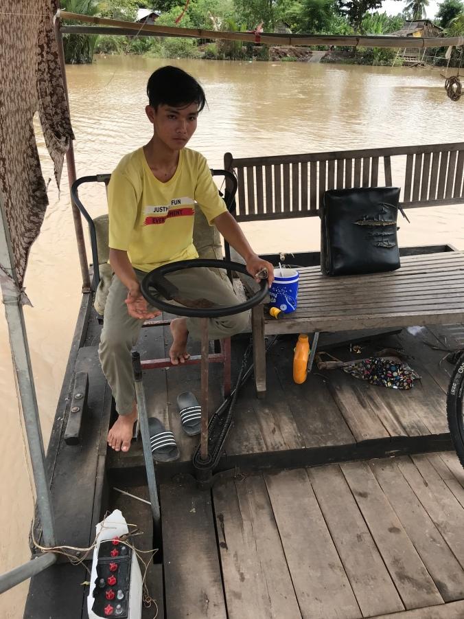 Gutt i gul t-skjorte styrer fergen.